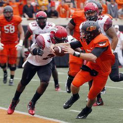 Oklahoma State quarterback J.W. Walsh (4) scores in front of Louisiana-Lafayette linebacker Delvin Jones (7) during the third quarter an NCAA college football game in Stillwater, Okla., Saturday, Sept. 15, 2012. Oklahoma State won 65-24.