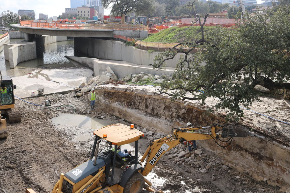 Photo of a construction site with a bulldozer hacking away at a limestone wall. Oak branches extend overhead. in the background is a diverted creek with a circular pavilion being built over it.