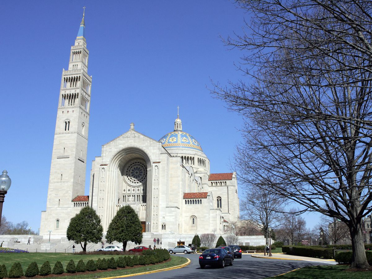 A giant basilica with a dome and a separate tower. Cars line up in the front driveway. The dome has blue hues.