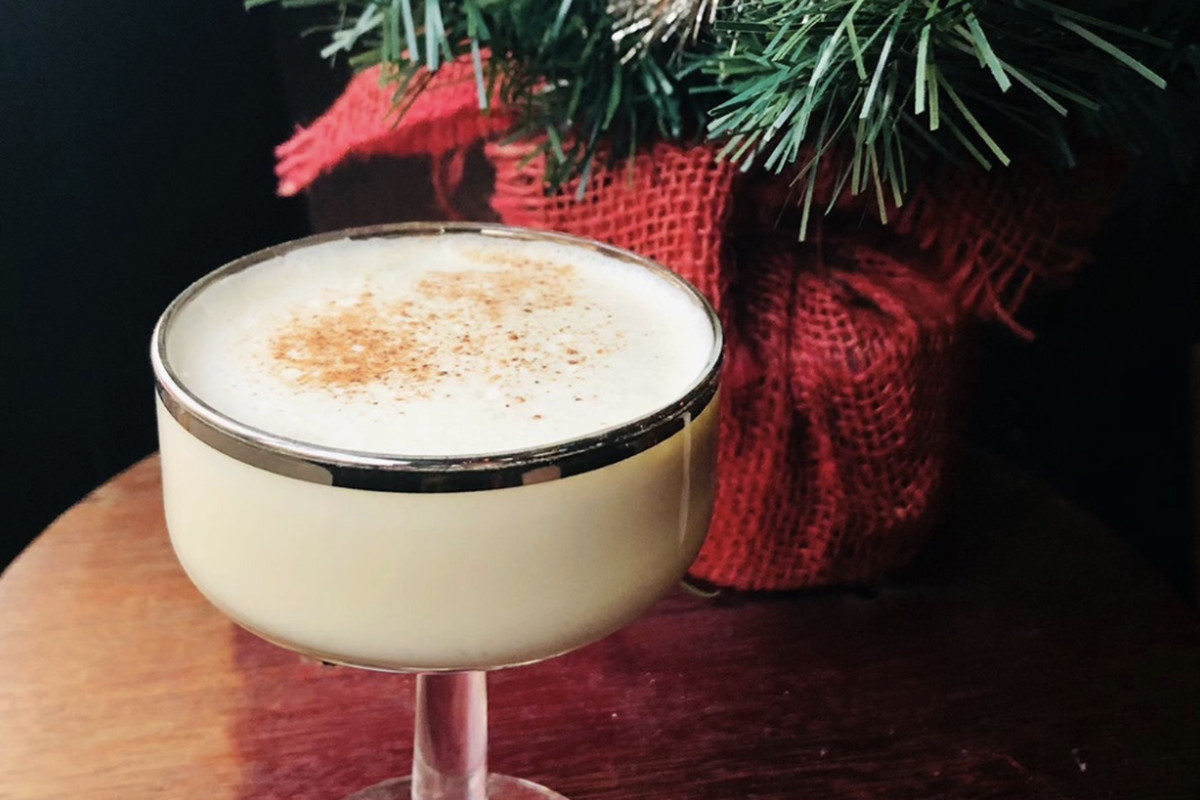 A glass of eggnog sprinkled with cinnamon and a Christmas wreath and red bow in the background