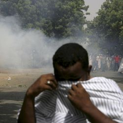 A Sudanese protester reacts to tear gas during a demonstration in Khartoum, Sudan, Friday, Sept. 14, 2012, as part of widespread anger across the Muslim world about a film ridiculing Islam's Prophet Muhammad. Germany's Foreign Minister says the country's embassy in the Sudanese capital of Khartoum has been stormed by protesters and set partially on fire. Minister Guido Westerwelle told reporters that the demonstrators are apparently protesting against an anti-Islam film produced in the United States that denigrates the Prophet Muhammad.