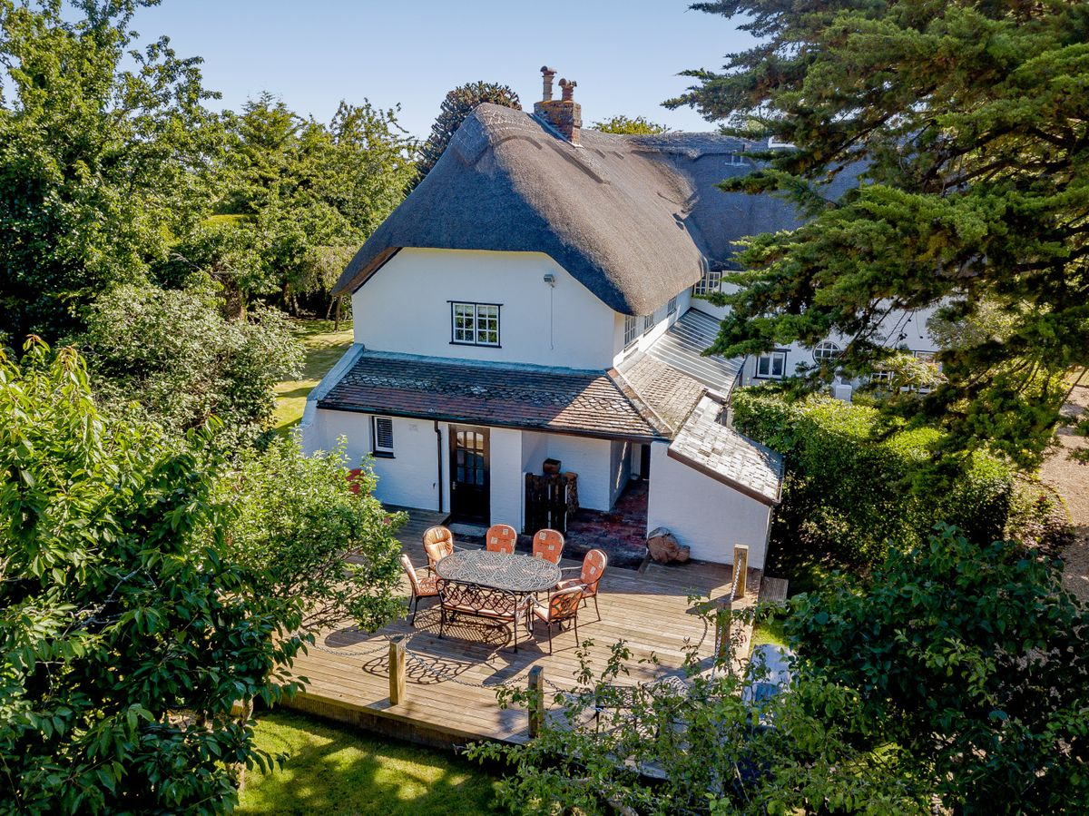 Exterior of cottage with thatched roof and outdoor dining area on a wooden deck.
