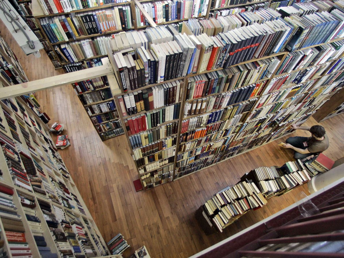The Strand Book Store in New York City. There are many books on tall shelves. A person is squatting looking at books on a lower shelf.