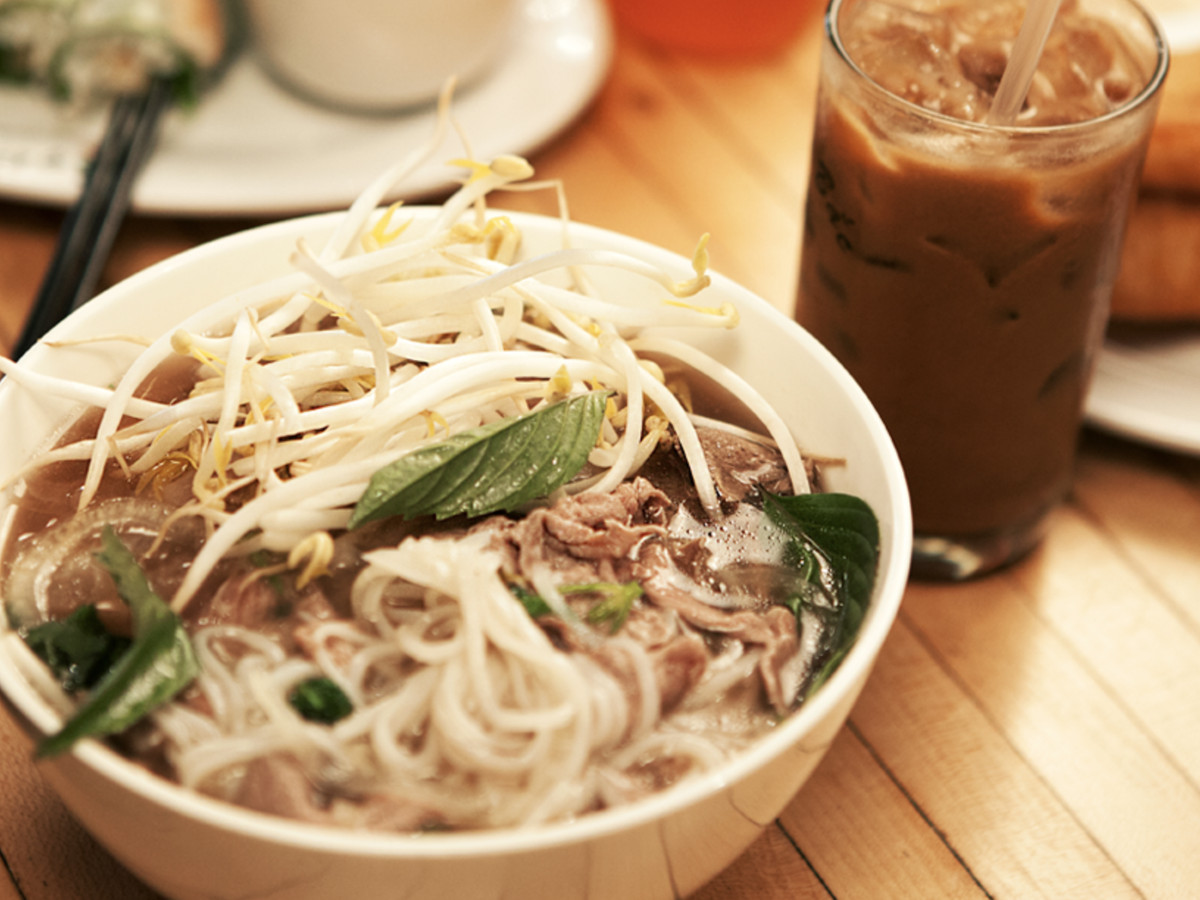 A bowl of pho at Pho Bac Sup Shop with iced coffee on the side.