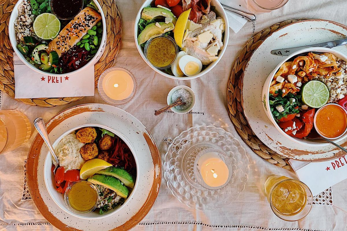 A Pret a Manger dinner spread, including a salmon rice bowl, a chipotle chicken rice bowl, and some obligatory avocado, laid out with candles