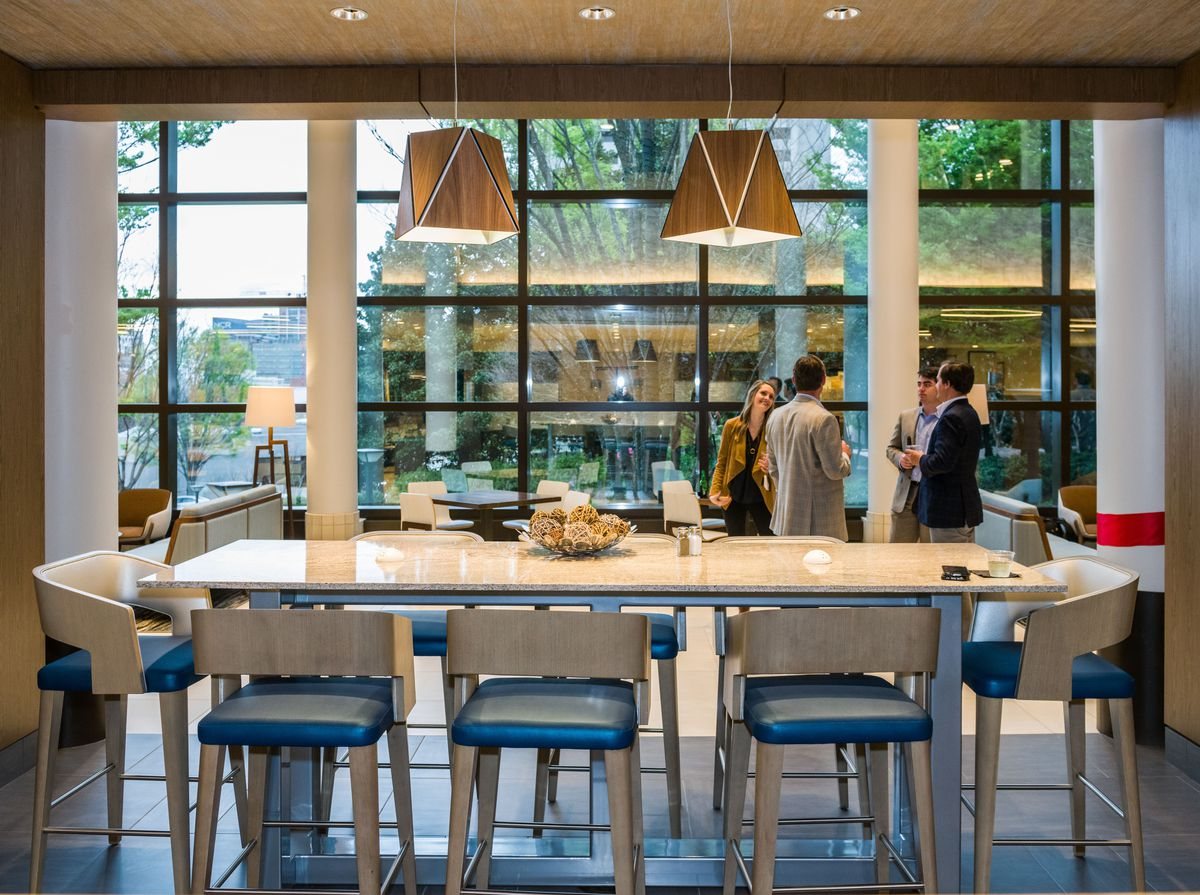 Another view of the food hall shows people chatting next to the seating area, a big window behind them looks out at trees in the yard.