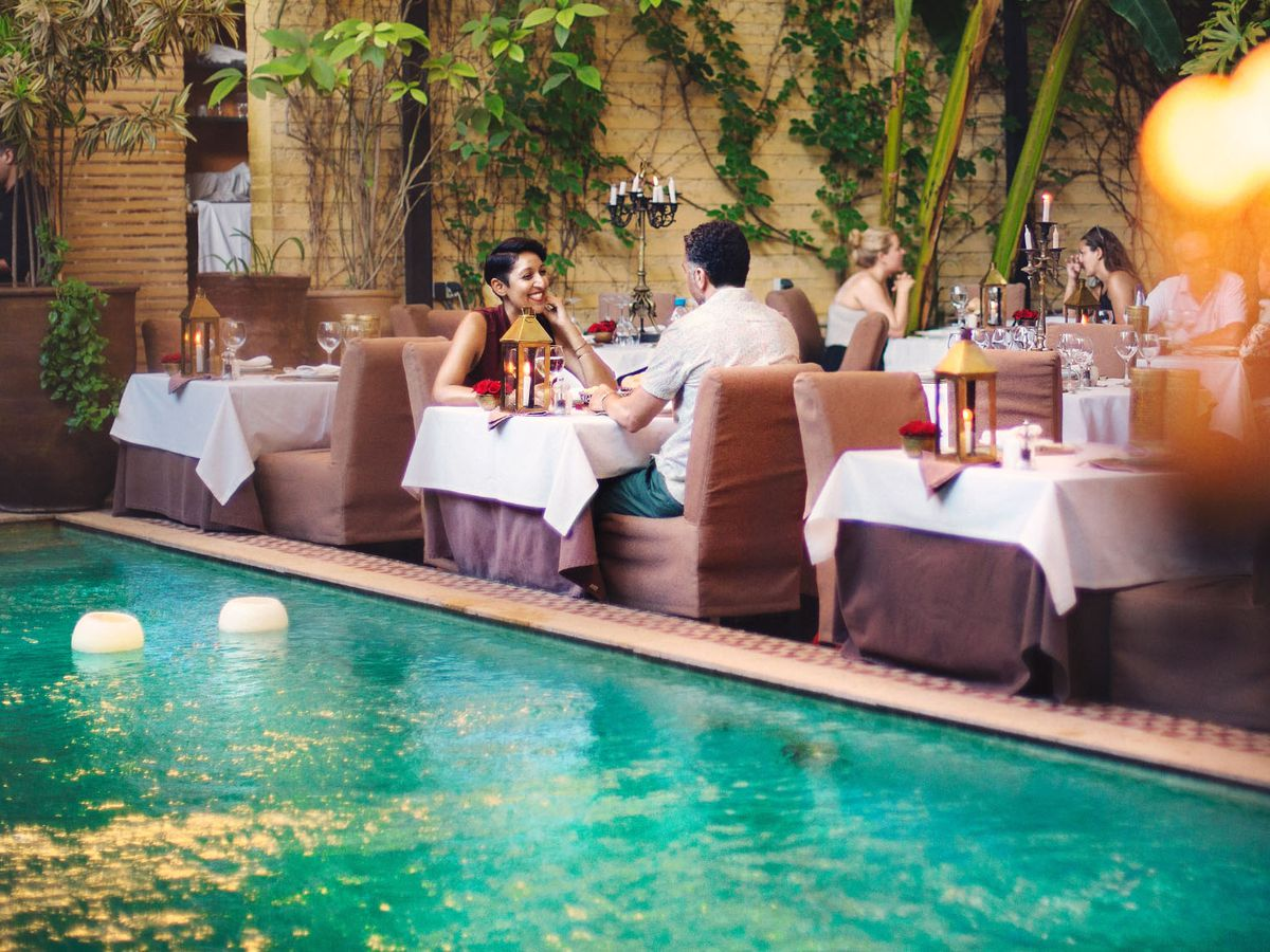 Guests sit at some of several set tables across a pool among lots of foliage