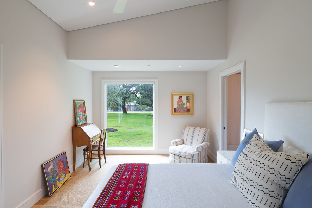 Light, minimalist bedroom with big picture window looking on to large lawn