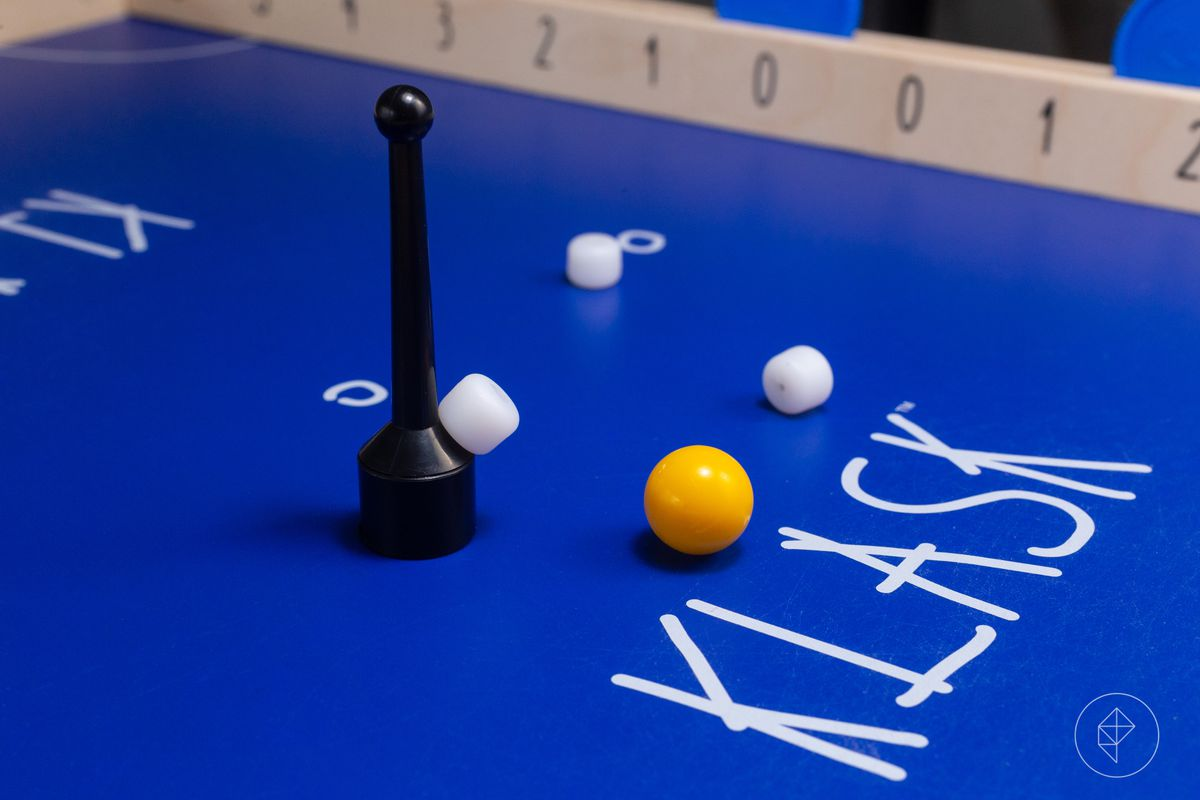 A close-up of the playing surface in Klask, showing the wear on the table from the striker sliding across the surface.