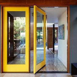 <strong>2. Statement-making entry</strong> | While nearly all multi-panel door styles work on the back of the house, pivot doors also pull double duty as dramatic front entry doors. Installed solo, paired with a fixed panel, or as functioning double doors, and painted a bright color, they point guests in the right direction, while ushering in plenty of fresh air. Add a smart lock to open and close the doors from your smartphone. <strong>Similar to shown:</strong> Pivot Door, from $2,300 per LF; <a class=