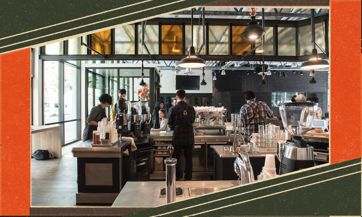 A barista stands in front of the espresso machines within the Marzocco space.