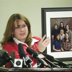 Shelby Gifford, family spokeswoman and friend of Susan Powell, who was reported missing Dec. 7, 2009, in Utah, talks to reporters about a photo of Powell, shown upper right, with her father, Chuck Cox, center, her mother Judy, lower right, and other family members, Thursday, Dec. 17, 2009, in Puyallup, Wash. Powell's family said Thursday they are saddened but not surprised that her husband Josh Powell has been named a person of interest in the investigation.