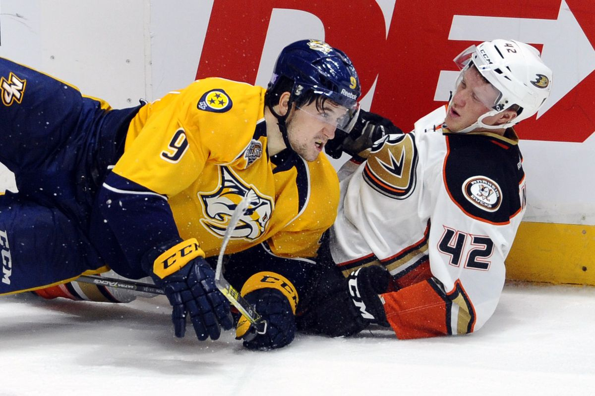 Josh Manson and Filip Forsberg go to the ice after a collision at Bridgestone Arena on Thursday.