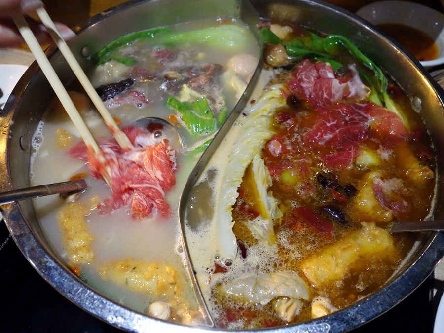 The regular and spicy broths in a silver bowl at Little Sheep.