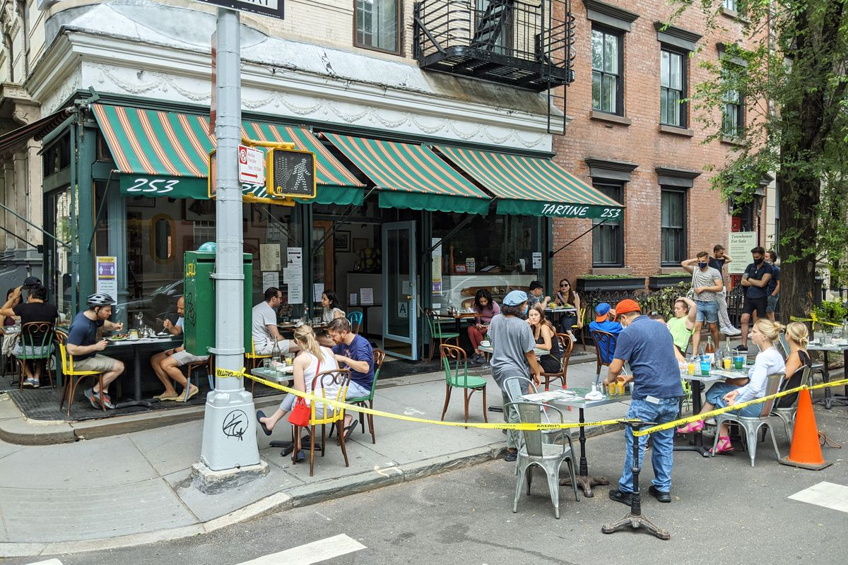 A bistro with seating in the street and a green awning.