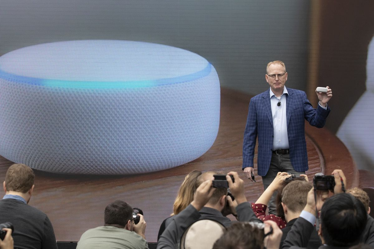 Dave Limp, Senior Vice President of Amazon Devices, stands onstage in front of a picture of a redesigned echo dot device.