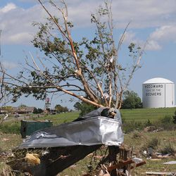 Debris wraps around trees along 34th Street after a severe thunderstorm spawned a massive tornado after midnight, Sunday, April 15, 2012 in Woodward, Okla. Five Northwest Oklahoma residents died during the storm.