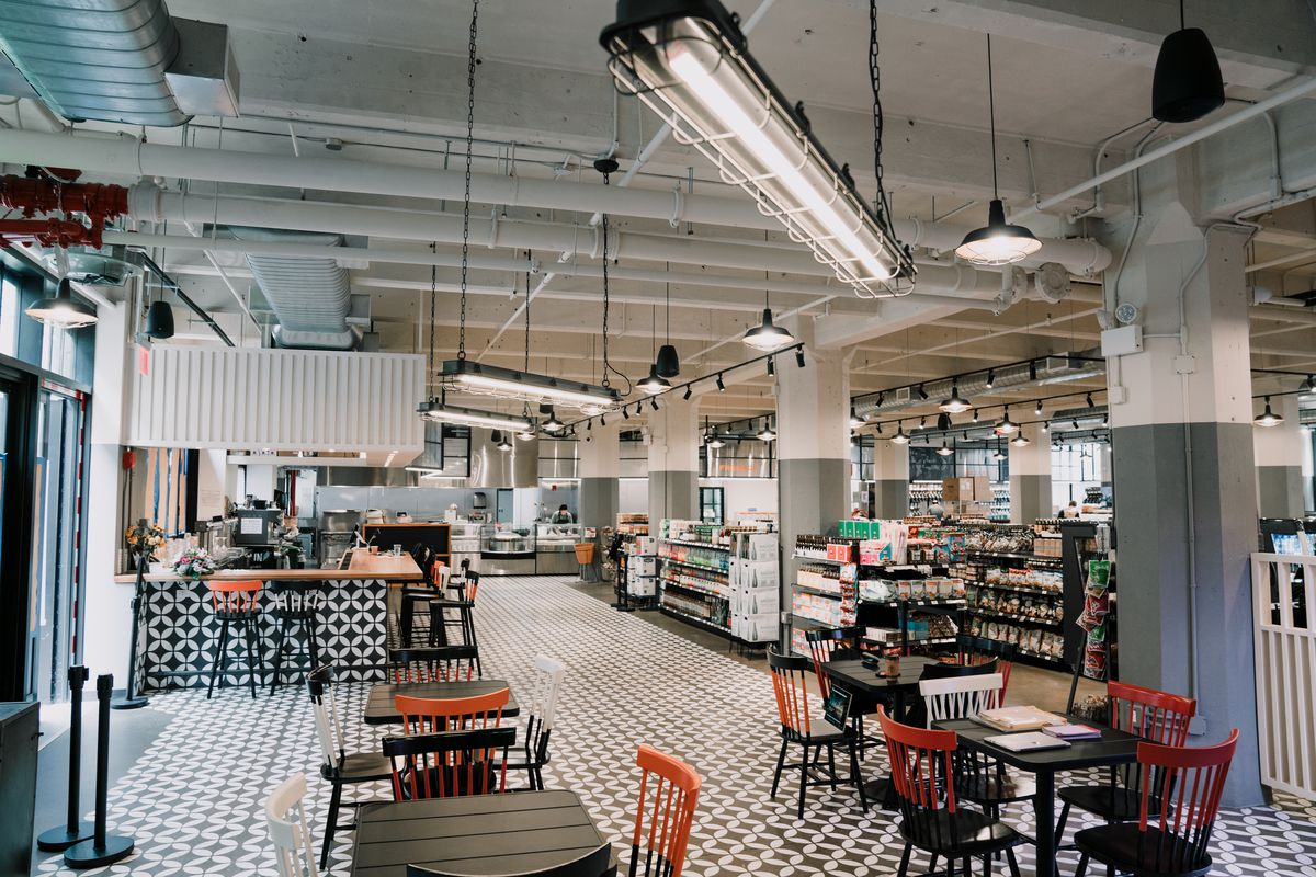 A modern, industrial-looking space with tables and isles of packaged foods
