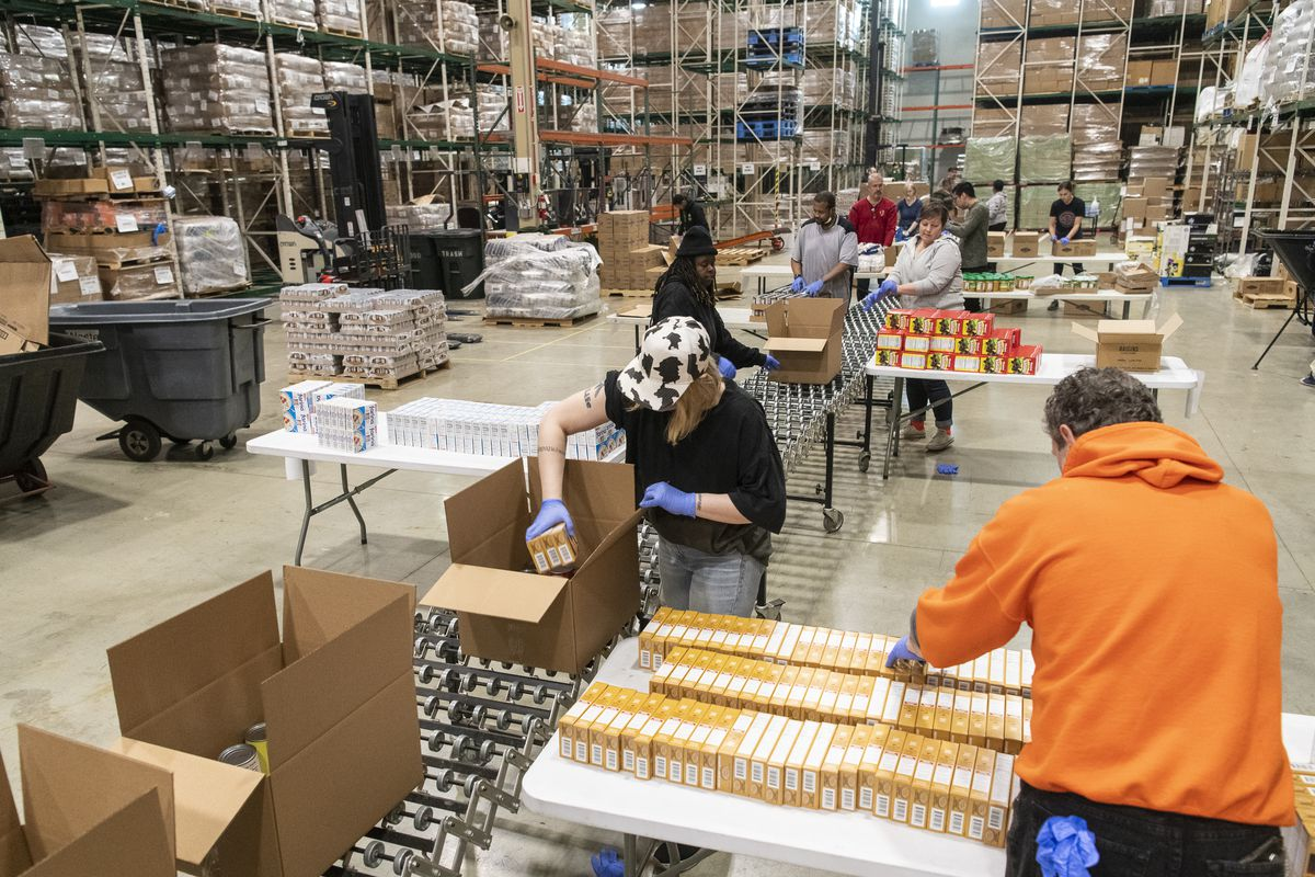 Volunteers help break down and repackage food at the Greater Chicago Food Depository, Tuesday, March 24, 2020.