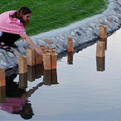 Jennifer de Tapia, of SLC, retrieves the luminaries from City Creek after floating them during a peace vigil which remembers 9/11 victims and victims of