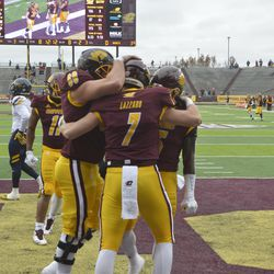 Tommy Lazzaro embraces teammates Steve Eipper and Jonathan Ward after scoring his second touchdown of the day.