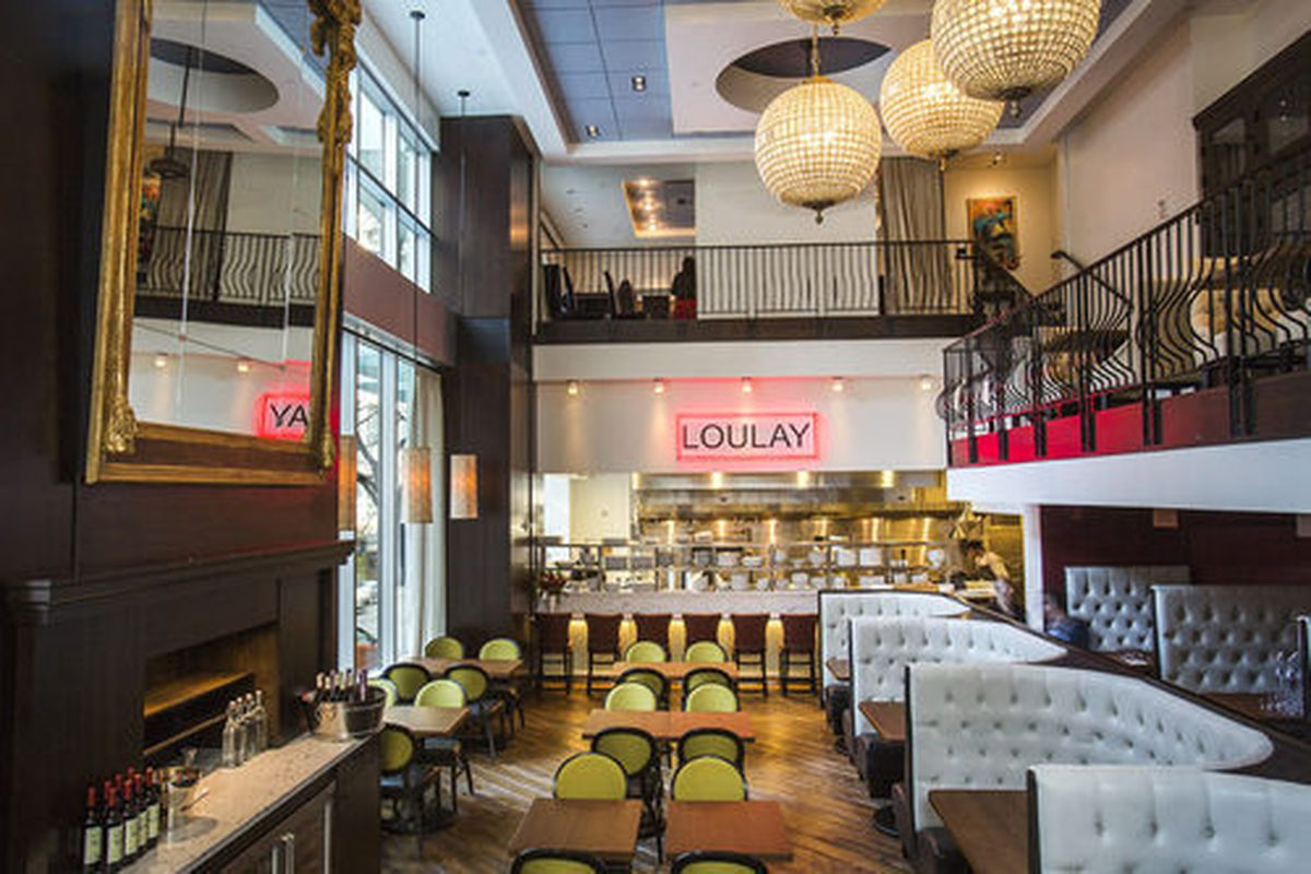 The high-ceilinged interior of Loulay Kithen and Bar, with balcony, light-gray booths, and large round chandeliers.