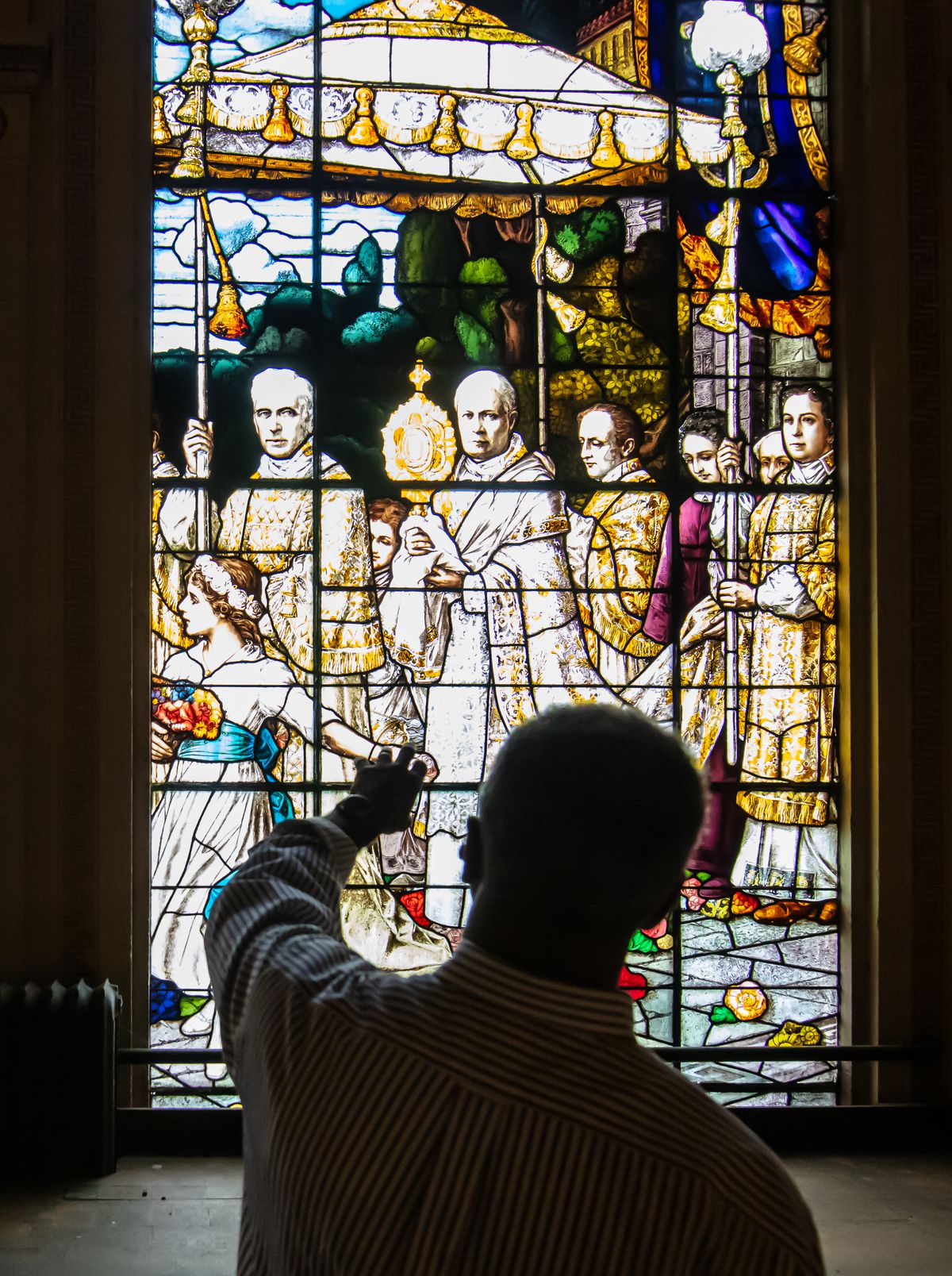 Church historian Larry Cope points out details of the F.X. Zettler-designed stained-glass windows.