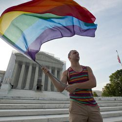 Gay rights advocate Vin Testa waves a rainbow flag in front of the Supreme Court at sun up in Washington, Wednesday, June 26, 2013. Justices are expected to hand down major rulings on two gay marriage cases that could impact same-sex couples across the country. One is a challenge to California's voter-enacted ban on same-sex marriage. The other is a challenge to a provision of federal law that prevents legally married gay couples from receiving a range of tax, health and pension benefits.