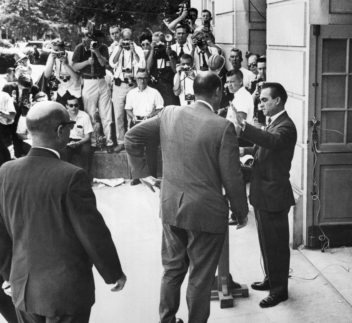 Jerry Falwell Sr. offered a platform to arch-segregationist George Wallace, shown here blocking a door at the University of Alabama.