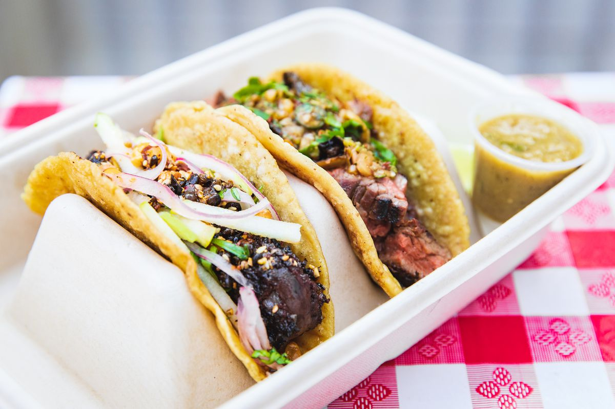 Two tacos with corn tortillas sitting in a tray.