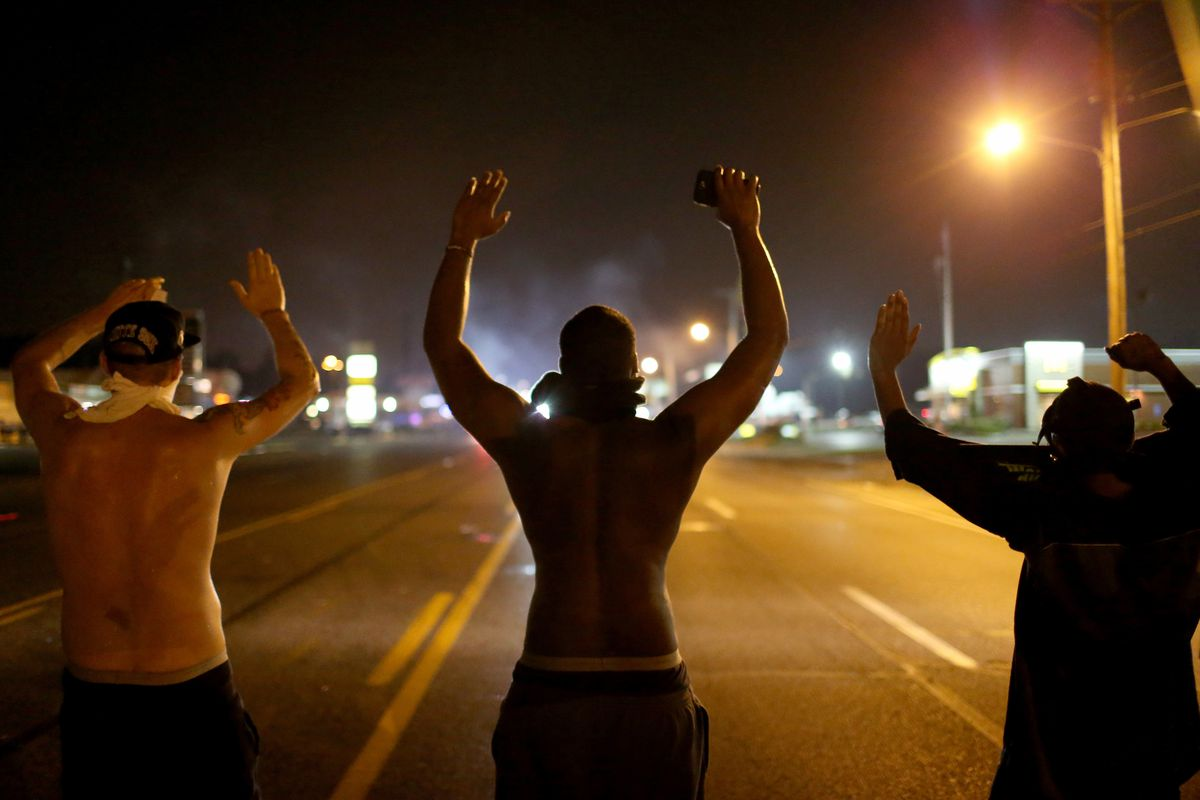 Ferguson demonstrators hold their hands up in protest of the shooting of Michael Brown.