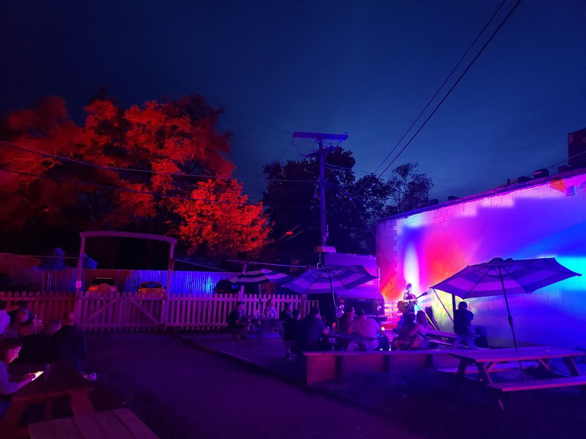 an outdoor wine garden with picnic tables, umbrellas, and eerie purple lighting at night