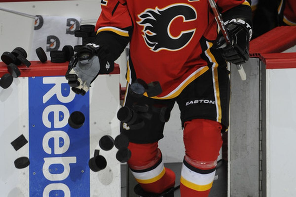 Jarome Iginla #12 of the Calgary Flames knocks the pucks down at the start of warm up. (Photo by Dale MacMillan/Getty Images)