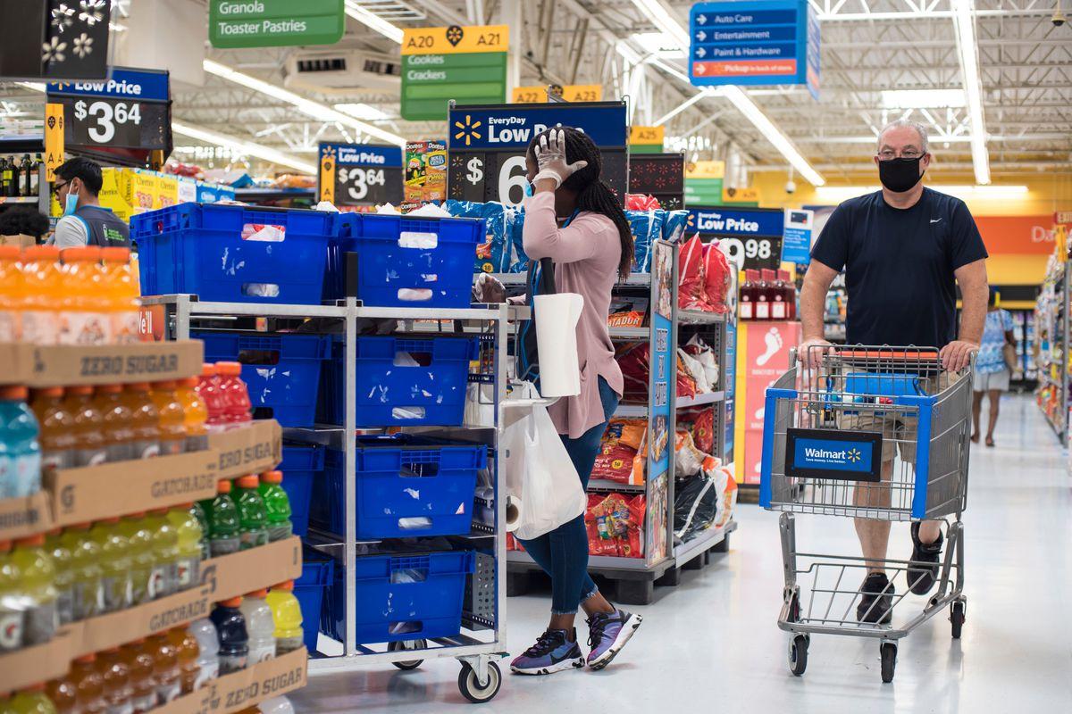 Shopper wearing face mask pushes a shopping cart through Walmart, walking by an employee wearing plastic gloves.