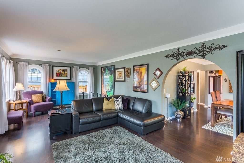 The living room in a Spanish Revival house features a large archway to the dining room