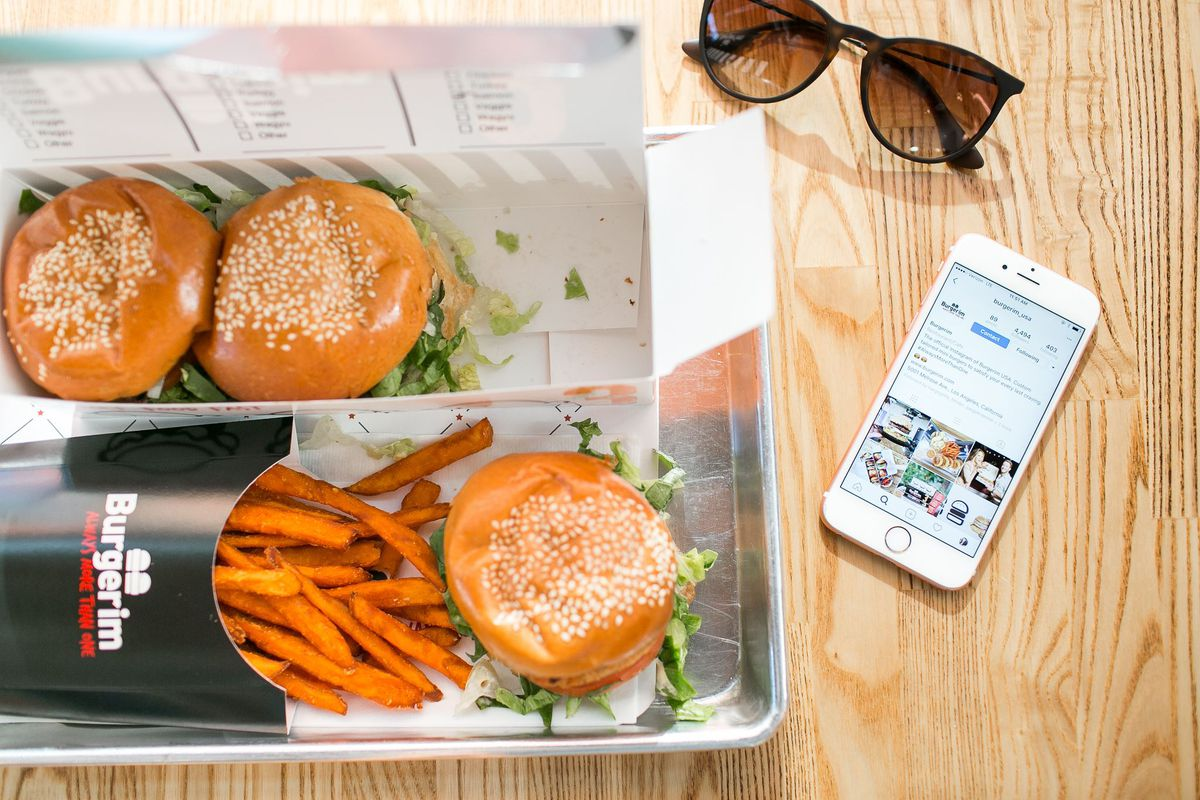 A tray of food and hip sunglasses and a phone on a table.
