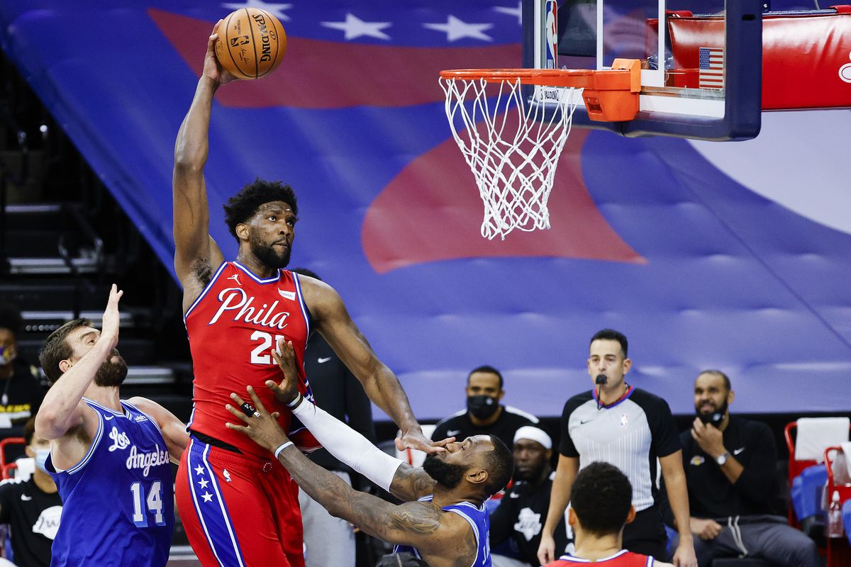 Joel Embiid of the Philadelphia 76ers drives to the basket over LeBron James of the Los Angeles Lakers during the fourth quarter at Wells Fargo Center on January 27, 2021 in Philadelphia, Pennsylvania.