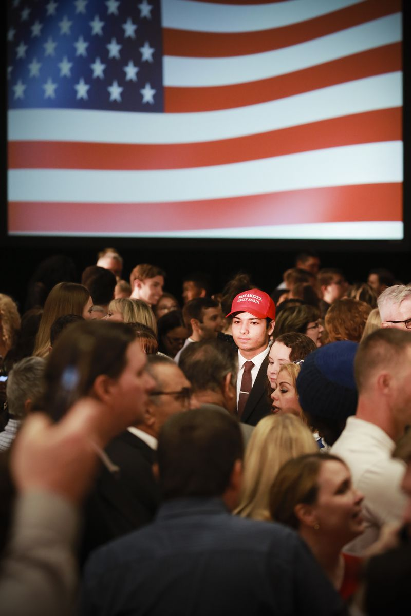 "A crowd in front of a screen showing an American flag at an election event with one person wearing a ""Make America Great Again"" hat."