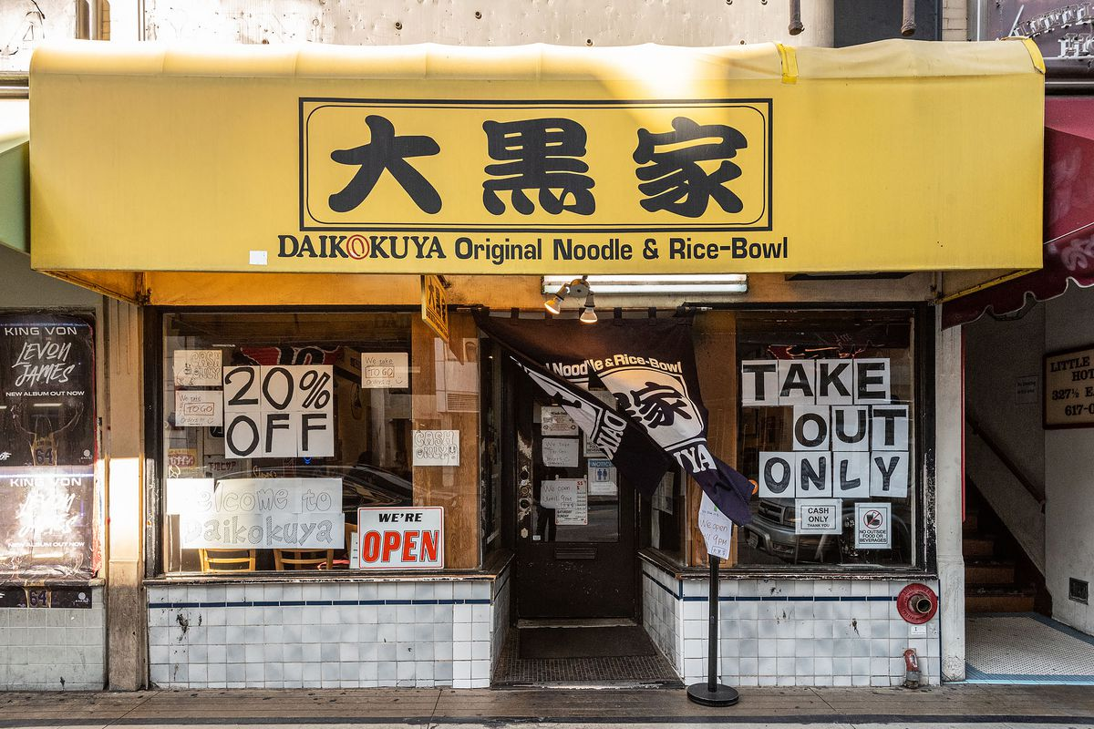 A yellow awning with discount signs at a ramen shop during coronavirus.
