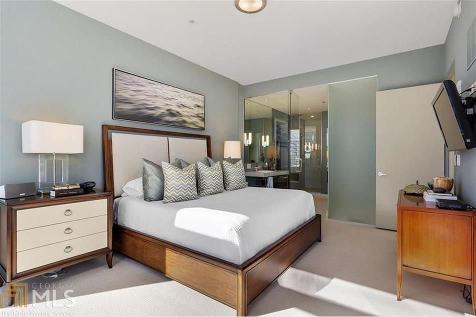 A master bedroom with gray walls and glass.