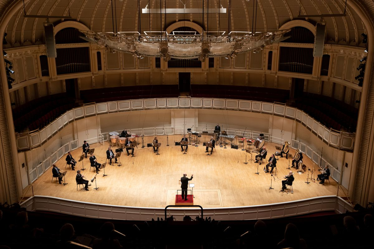 On Thursday night, musicians of the Chicago Symphony Orchestra —spread across the stage to maintain social distancing measures —under the direction of trombonist Michael Mulcahy, perform the first live concert in more than a year with an audience in attendance at Orchestra Hall.
