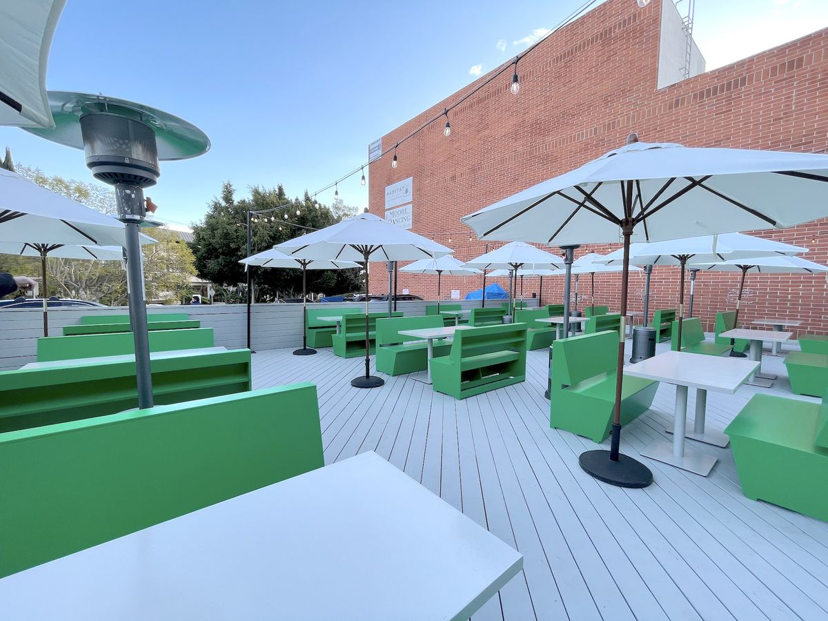 An outdoor patio with bright green booths and string lights during COVID.