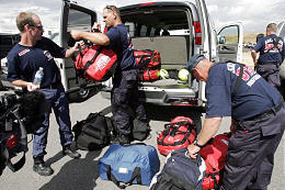 John Maddux, left, Michael Stevens and James DeGering load vans for Hurricane Rita relief.