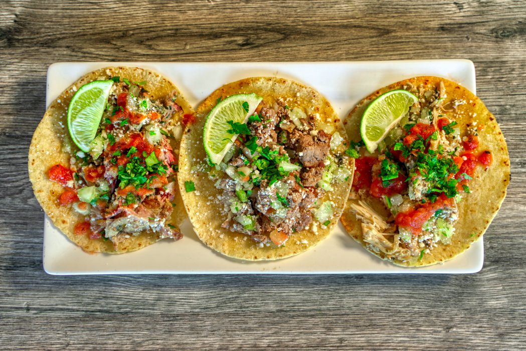 Three open tacos on a white plate
