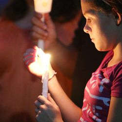 Danielle Sidwell, cousin to Sgt. Derek Johnson, holds candle during a vigil held in his honor   in Draper Sunday, Sept. 1, 2013. Johnson was shot and killed this morning.