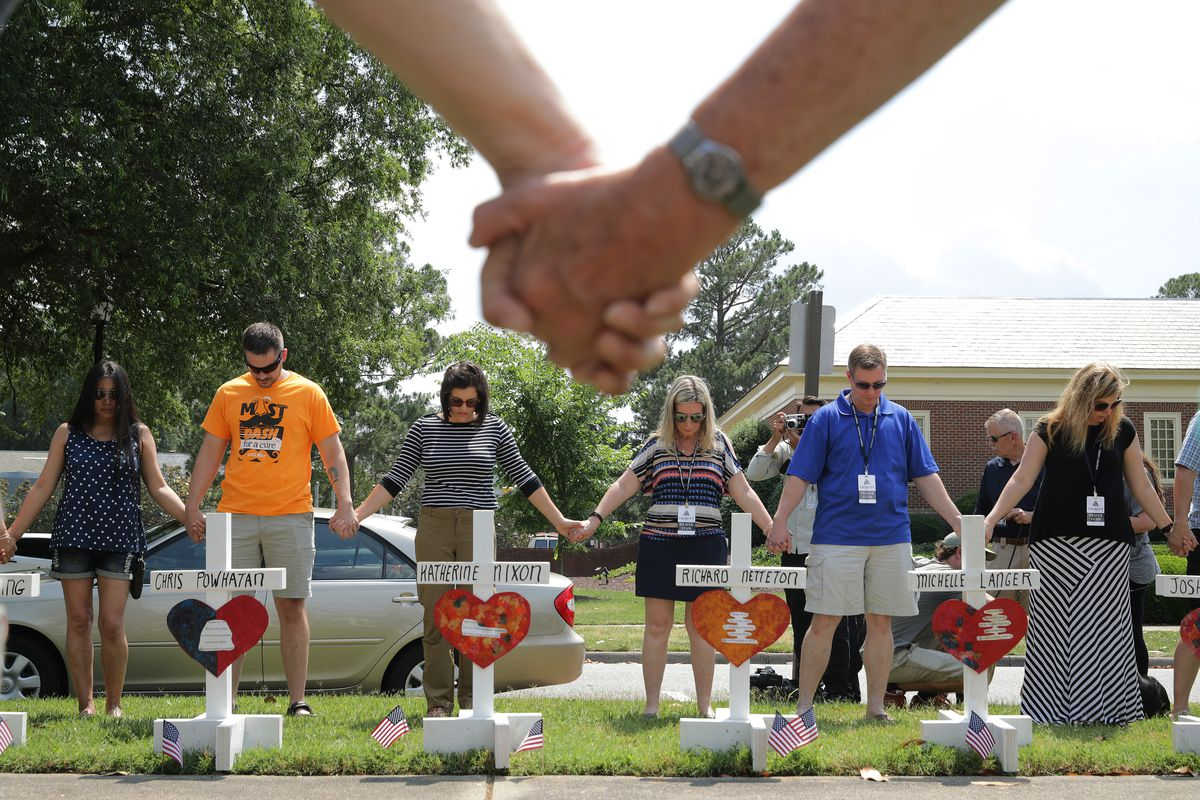 People hold hands and pray together at a makeshift memorial for the 12 victims of a mass shooting at the Municipal Center June 02, 2019 in Virginia Beach, Virginia.