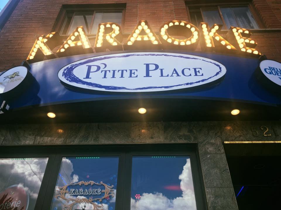 A lit-up karaoke sign over the bar entrance.