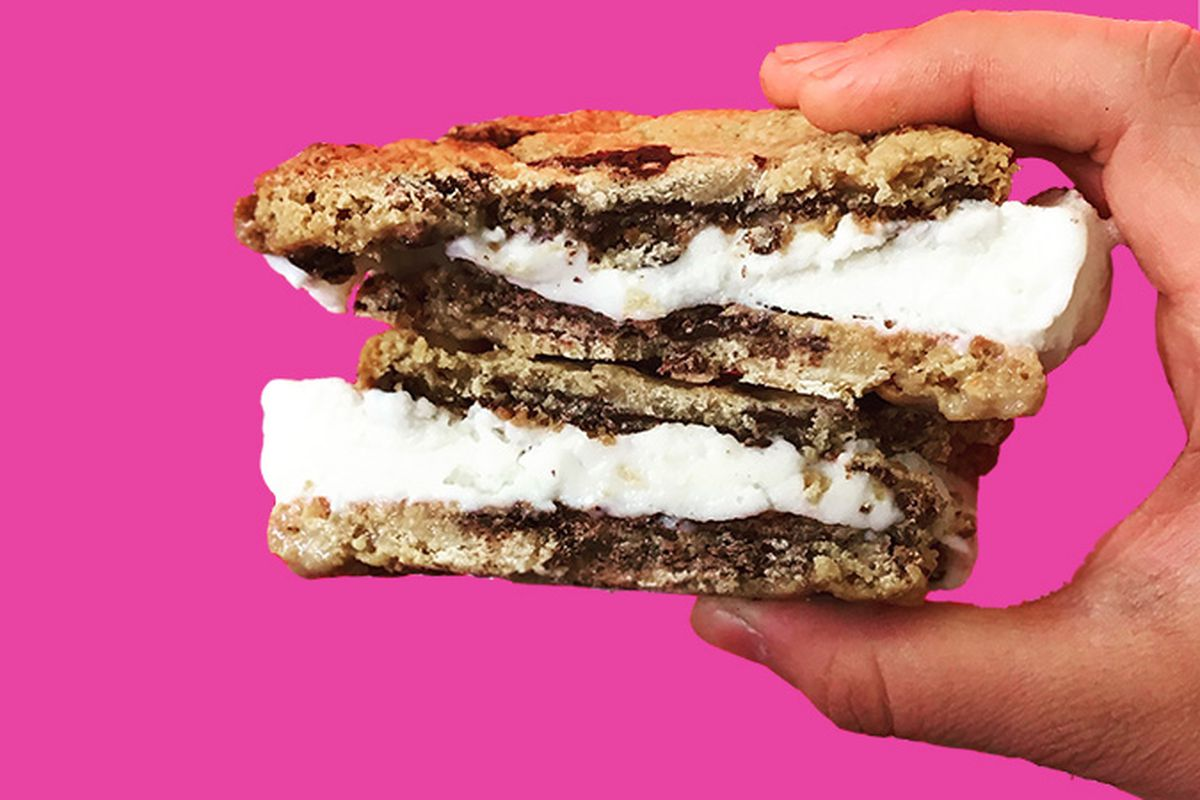 A hand holds two sandwiches, chocolate chip cookies with a layer of ice cream in the middle.
