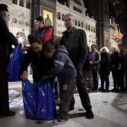 Father Andreas, an Orthodox Christian priest hands out food parcels at Piraeus Cathedral, near Athens on Tuesday, April 10, 2012.  The Orthodox church has stepped up a charity drive to help the unemployed in the crisis-hit country ahead of Orthodox Easter on upcoming Sunday.
