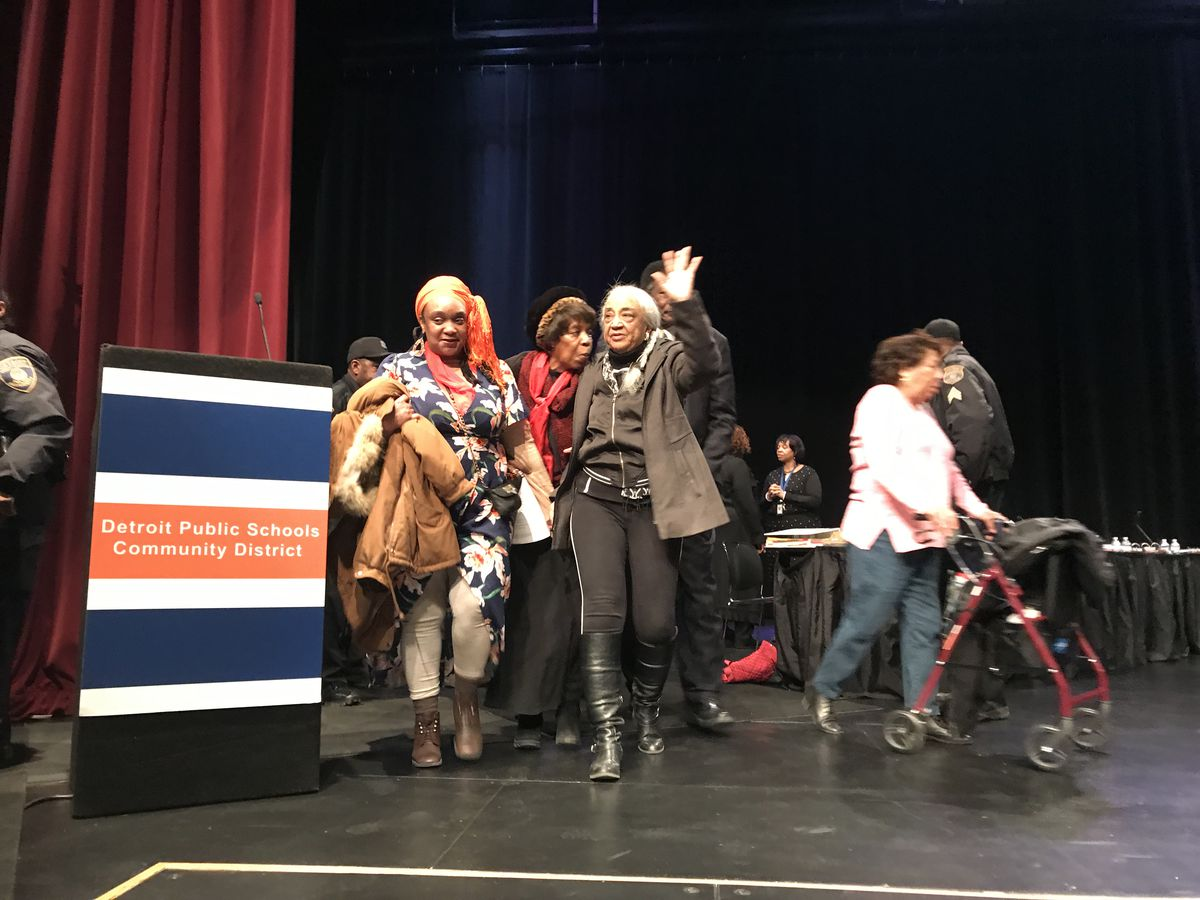 Detroit activist Helen Moore waved to her fellow activisits from the stage at Mumford High School. She returned to the room after her removal from the auditorium prompted loud objections that led to a school board meeting's abrupt ending on March 13, 2018.